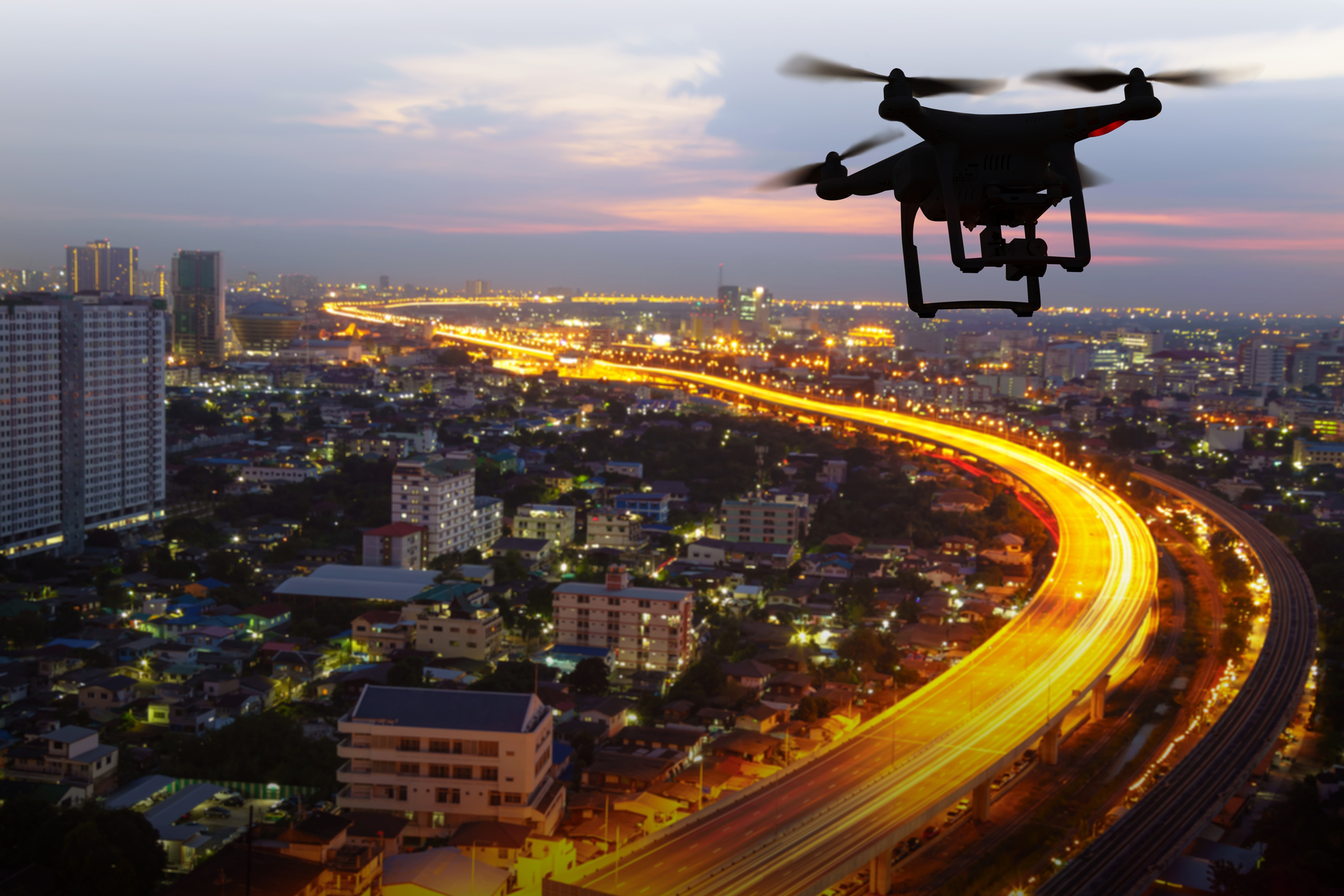 silhouette-of-drone-flying-above-city-at-sunsetjpg