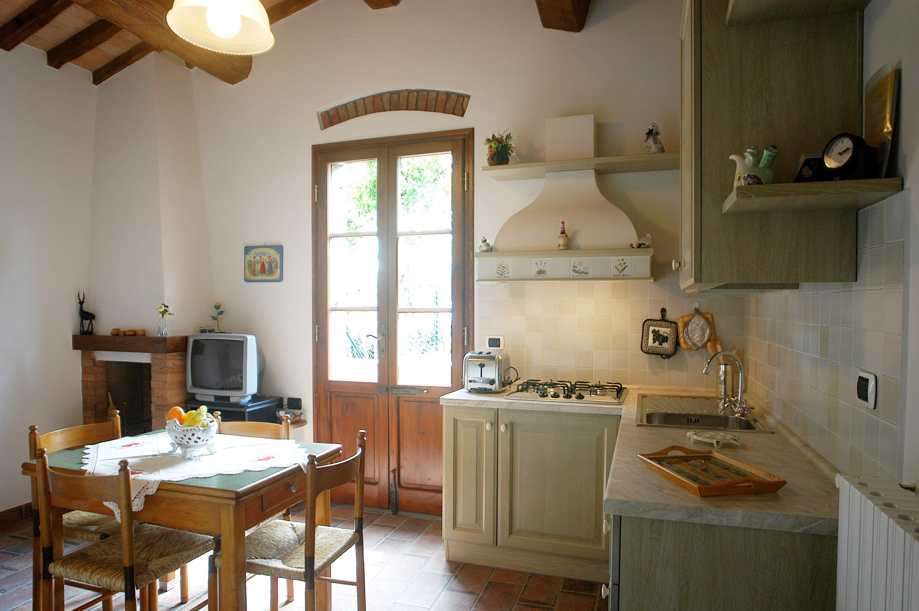 living room with kitchenette and fireplace farmholiday San Gimignano